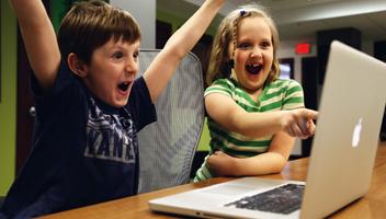 Två barn jublar framför en dator