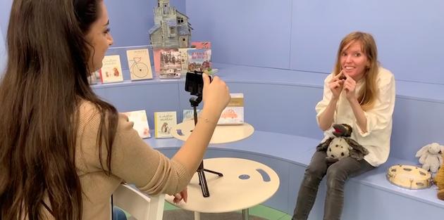 En bibliotekarie gör figurer med händerna till en sång, på pekboksklubb för småbarn via Zoom