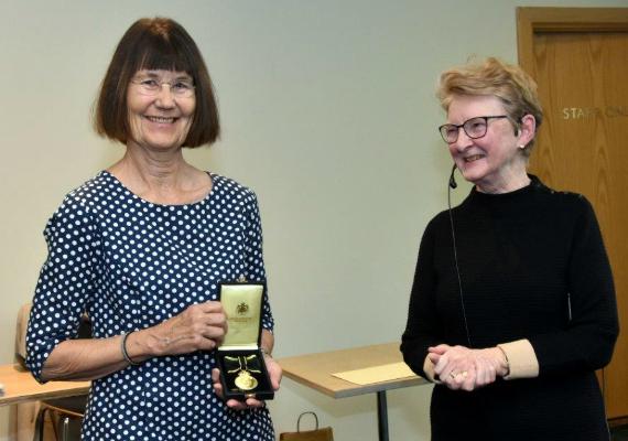 Gunilla Lundgren håller upp medaljen bredvid Marianne af Malmborg.