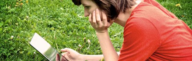 Kvinna ligger i gräset och läser e-bok