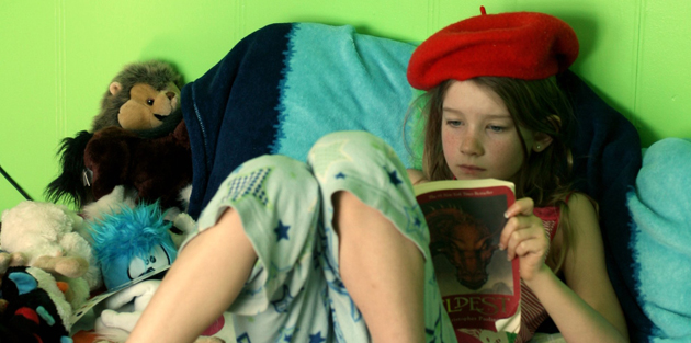 Flicka som sitter i en säng och läser en bok