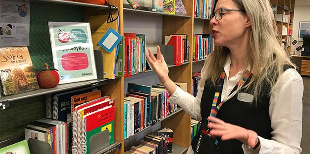 Bibliotekarie Lynn Alpberg framför en bokhylla.