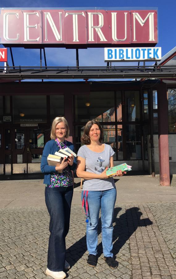 Två bibliotekarier i solen utanför Årsta bibliotek.