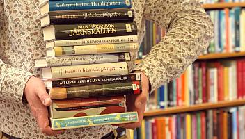 En person på biblioteket bär en trave böcker