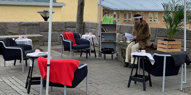 Bibliotekarie med visir håller i poesicirkel för seniorer