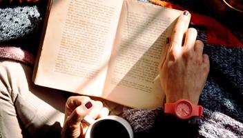 Uppslagen bok med en hand som ska vända blad och en hand som håller en kaffekopp
