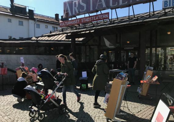 Människor i solljus utanför Årsta bibliotek.